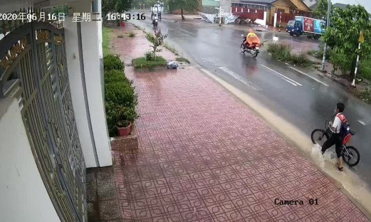 Cậu bé móc rác ở miệng cống dưới mưa