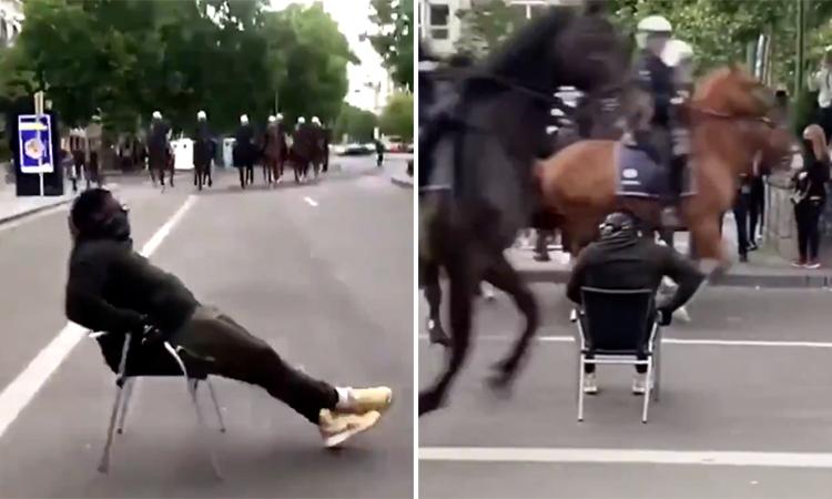 Ngồi bình thản giữa đường khi cảnh sát lao ngựa đến